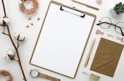 Mockup with envelope, clip board,cotton flowers,glasses and golden accessories arranged and ordered. Home office. Home office workspace mockup with envelope Stock Photography