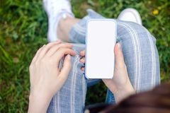 Mockup of female hand holding cell phone with blank screen stock image