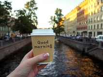 Mockup of female hand holding a coffee paper takeaway cup on the river background with copy space. Close-up view of disposable paper cup of coffee in woman`s stock photo