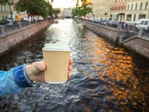Mockup of female hand holding a coffee paper takeaway cup on the river background with copy space. Close-up view of disposable paper cup of coffee in woman`s royalty free stock photo