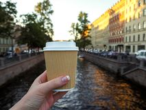 Mockup of female hand holding a coffee paper takeaway cup on the river background with copy space. Close-up view of disposable paper cup of coffee in woman`s royalty free stock images