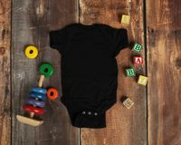Mockup Flat Lay of black baby bodysuit shirt. On rustic wood background with wooden blocks and baby toys royalty free stock photos