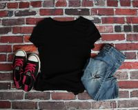 Mockup Flat Lay of Black T shirt. With black canvas shoes and ripped jeans on a brick background stock photo