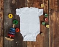 Mockup Flat Lay of white baby bodysuit shirt. On rustic wood background with wooden blocks and baby toys royalty free stock images