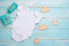 Mockup Flat Lay white baby shirt with wooden toys on a blue background. Layout for the design and placement of logos, advertising