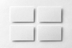 Mockup of four white business cards arranged in rows at white de. Sign paper background Royalty Free Stock Photography