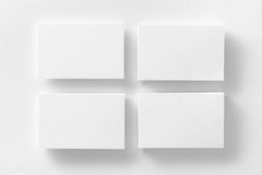 Mockup of four white business cards stacks arranged in rows at w. Hite design paper background Royalty Free Stock Images