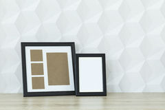 Mockup frames on a desk. Two mockup frames on wooden desk against white wall Stock Photos