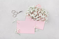 Mockup of gypsophila flowers in envelope and pink paper card on light table top view in flat lay style. Royalty Free Stock Photography