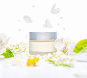 Mockup of hand, facial or body cream with spring flowers, concep Stock Photo
