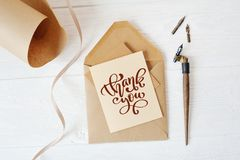 Mockup holiday letter Blank paper and an envelope with pen on wood table with calligraphic text Thank you, Lettering Stock Image