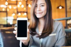 Asian beautiful business woman holding and showing white mobile phone with blank black screen and smiley face in cafe. Mockup image of an Asian beautiful royalty free stock images