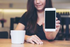 Asian beautiful woman holding and showing white mobile phone with blank black screen and white coffee coupon wooden table in cafe. Mockup image of an Asian Royalty Free Stock Photo