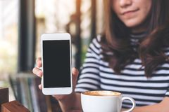 Mockup image of a beautiful woman holding and showing white mobile phone with blank black screen and coffee cup on table. In cafe Royalty Free Stock Photo