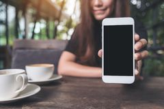 Mockup image of a beautiful woman holding and showing white mobile phone with blank black screen with coffee cups. On vintage wooden table Stock Photos