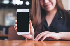 Mockup image of a beautiful woman holding and showing white mobile phone with blank black screen with smiley face and coffee cup o Stock Image
