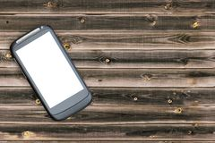 Mockup image of black mobile smartphone with blank white screen on vintage brown wood table background. Mock up of application wit. H copy space Royalty Free Stock Photo