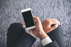 Mockup image of a business man sitting and holding white mobile phone with blank black screen with gray rug Stock Image