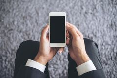 Mockup image of a business man sitting and holding white mobile phone with blank black screen with gray rug Stock Images