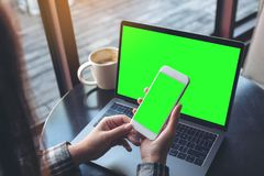 Mockup image of business woman holding mobile phone with blank green screen while using laptop on wooden table. In cafe Royalty Free Stock Photo