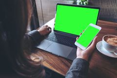 Mockup image of business woman holding mobile phone with blank green screen while using laptop on wooden table. In cafe Stock Photography