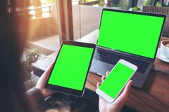 Mockup image of a businesswoman holding white mobile phone , black tablet and laptop with blank green screen on vintage wooden tab. Le with coffee cup in cafe Royalty Free Stock Photo