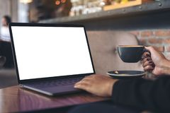 A businesswoman using laptop with blank white desktop screen while drinking hot coffee on wooden table in cafe Royalty Free Stock Photos