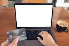 Mockup image of a hand holding credit card while using and typing on laptop with blank white screen and coffee cup. On wooden table in modern loft cafe Stock Photo