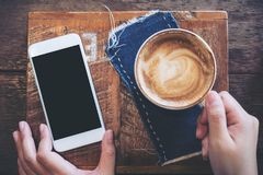 Mockup image of a hand holding mobile phone with blank black screen and coffee cup. On vintage wooden table in cafe Stock Photo