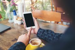 A hand holding and pointing at white mobile phone with blank black desktop screen with yellow coffee cup on wooden table in cafe. Mockup image of a hand holding stock image