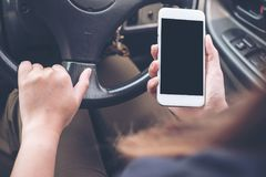 A hand holding and using white mobile phone with blank black desktop screen while driving car on the road. Mockup image of a hand holding and using white mobile Stock Images