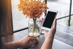 Mockup image of a hand holding white mobile phone with blank black screen with laptop and flower vase on vintage wood table Stock Photos