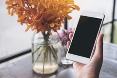 Mockup image of a hand holding white mobile phone with blank black screen with laptop and flower vase on vintage wood table Royalty Free Stock Photos