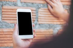 Hand holding white mobile phone with blank black screen while lean on brick wall background. Mockup image of hand holding white mobile phone with blank black Royalty Free Stock Photos