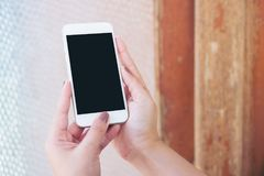 Hand holding white mobile phone with blank black screen and vintage glass mirror background. Mockup image of hand holding white mobile phone with blank black stock photo