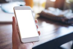 Mockup image of a hand holding white mobile phone with blank screen. In vintage cafe Stock Image