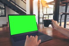 Mockup image of a hand using and touching laptop with blank green screen while drinking coffee on wooden table. In cafe Royalty Free Stock Photos