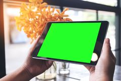 Mockup image of hands holding black tablet pc with blank green screen and flower vase on wooden table Royalty Free Stock Images