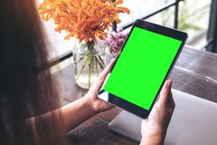 Mockup image of hands holding black tablet pc with blank green screen and flower vase on wooden table. In cafe Royalty Free Stock Images
