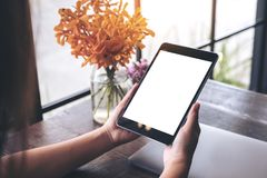 Mockup image of hands holding black tablet pc with blank white screen and flower vase on wooden table Stock Photography
