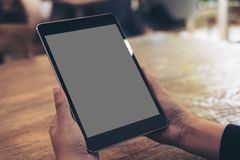 Mockup image of hands holding black tablet pc with gray blank screen on wooden table background. In cafe Stock Photo