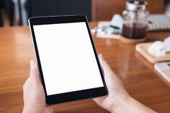 Mockup image of hands holding black tablet pc with white blank screen on wooden table background Royalty Free Stock Images