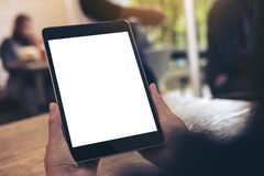 Mockup image of hands holding black tablet pc with white blank screen on wooden table with many people Stock Image