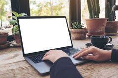 Mockup image of hands using and typing on laptop with blank white desktop screen on vintage wooden table. In cafe royalty free stock photography