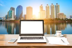 Mockup image of laptop with blank white screen on wooden table view outdoors of office building cityscape background. Stock Image