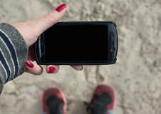 Mockup image of lay down and hand holding black mobile phone with blank screen on the background of sand. stock photos