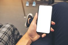 A man`s hand holding black mobile phone with blank screen in subway royalty free stock images
