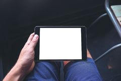 A man`s hand holding black tablet pc with blank white screen on thigh stock photos