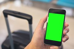 Mockup image of a man`s hand holding and using black mobile phone with blank green screen. With black baggage in airport Royalty Free Stock Photo
