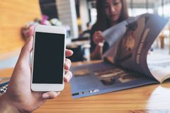 Mockup image of a man`s hand holding white mobile phone with blank black screen in modern cafe and blur woman reading newspaper Stock Images
